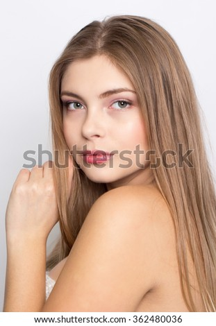 Portrait of a beautiful young blonde girl on a white background.