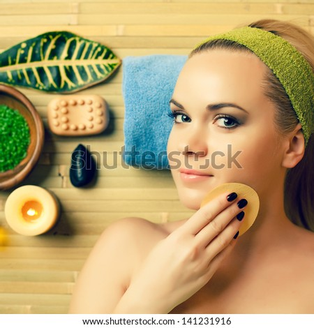 Portrait of a beautiful young blonde touching her face with a special sponge at a spa salon. Perfect young skin. Skincare and haircare. Close up. Indoor shot - stock photo