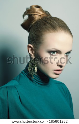 Portrait of a beautiful young blonde wearing green (blue) dress and ethnic earrings. Model posing over light-blue background. Perfect skin and stylish hairdo. Studio shot - stock photo