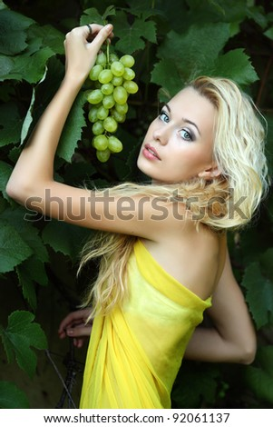 portrait of a beautiful young blonde with a bunch of grapes - stock photo