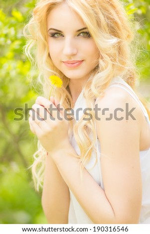 Portrait of a beautiful young blonde woman with dandelions. Girl posing in nature and smiling