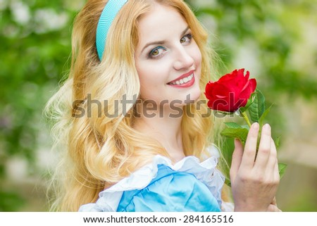 Portrait of a beautiful young blonde woman with long hair dressed as Alice in Wonderland.The girl is holding a red rose. Soft focus