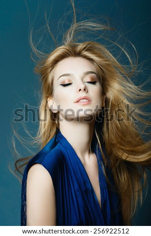 Portrait of a beautiful young blonde woman with long hair in a studio on a blue background - stock photo