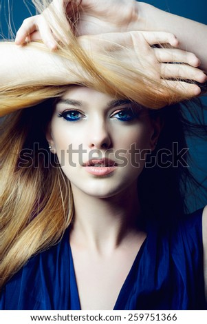 Portrait of a beautiful young blonde woman with long hair in a studio on a blue background, close up - stock photo