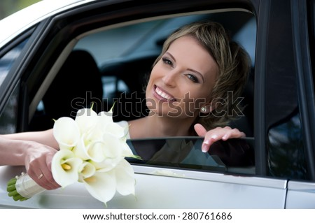 Portrait of a beautiful young blonde woman with short hair (the bride) with a bouquet of lilies in the car - stock photo