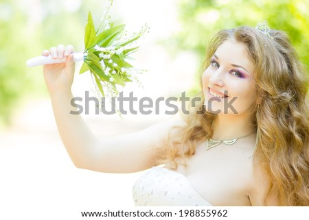 Portrait of a beautiful young bride in nature in a magnificent wedding dress.