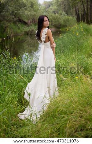 Portrait of a beautiful young bride wearing a slinky dress on the bank of the river in foliar summer forest