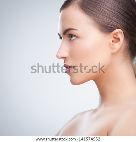 Portrait of a beautiful young brunette posing topless in front of a tray background. - stock photo