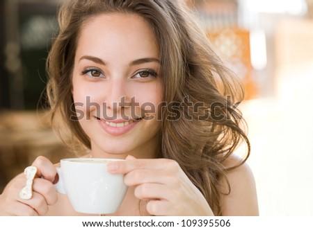 Portrait of a beautiful young brunette woman enjoying coffee. - stock photo