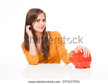 Portrait of a beautiful young brunette woman holding orange piggy bank. - stock photo