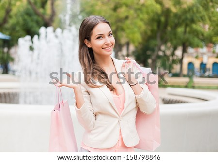 Portrait of a beautiful young brunette woman holding shopping bags. - stock photo