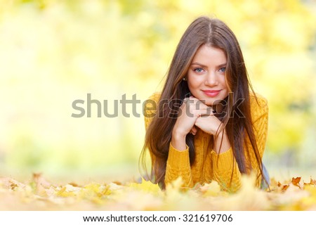 Portrait of a beautiful young brunette woman laying in the autumn park - stock photo