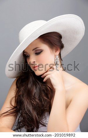 Portrait of a beautiful young brunette woman. Wearing white hat over long loose curly hair. Open shoulders summer dress. Against grey studio background.  - stock photo