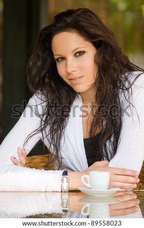 Portrait of a beautiful young brunette woman with a cup of coffee. - stock photo