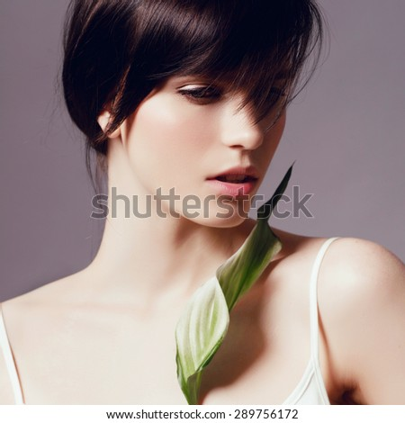 Portrait of a beautiful young brunette woman with a green leaf in the studio, the concept of beauty and health, close up - stock photo