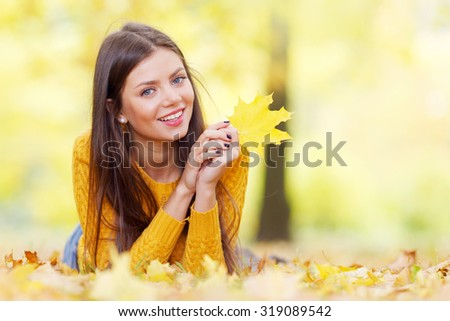 Portrait of a beautiful young brunette woman with autumn maple leaf - stock photo