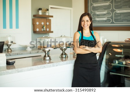 Portrait of a beautiful young business owner standing in front of her bakery and smiling - stock photo