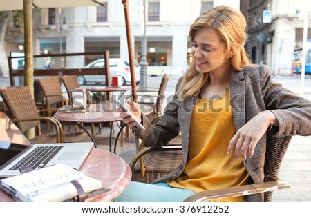 Portrait of a beautiful young business woman at coffee shop terrace with laptop computer, using a smart phone to work. Professional smiling woman drinking coffee using technology, outdoors lifestyle. - stock photo