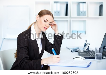 Portrait of a beautiful young business woman in the office doing some paperwork - stock photo