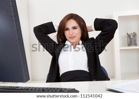Portrait of a beautiful young businesswoman at desk relaxing - stock photo