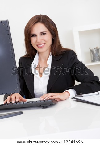 Portrait of a beautiful young businesswoman at desk using computer - stock photo