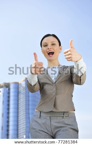 Portrait of a beautiful young businesswoman celebrating. Outside background. Thumbs up. - stock photo