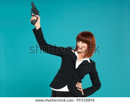portrait of a beautiful, young businesswoman, pointing a gun in the air, to start a compettion, on blue background