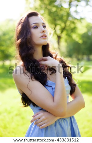 Portrait of a beautiful young Caucasian woman in a spring garden. Sweet girl, clean skin, long dark hair. - stock photo