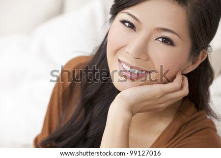 Portrait of a beautiful young Chinese Asian Oriental woman resting on her hand - stock photo