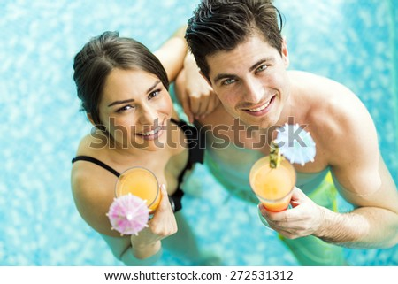 Portrait of a beautiful young couple smiling and drinking a cocktail in a pool - stock photo