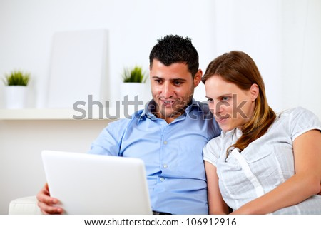 Portrait of a beautiful young couple using laptop together at home indoor - stock photo