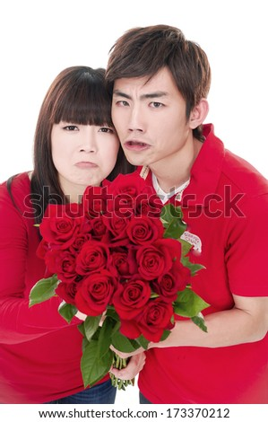 Portrait of a beautiful young couple with bouquet of red roses - stock photo