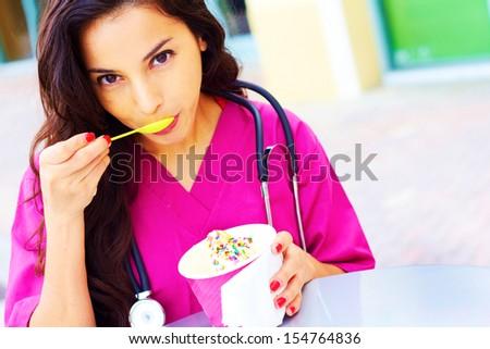 Portrait of a beautiful young female doctor having frozen yogurt. Horizontal shot. - stock photo