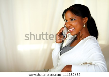 Portrait of a beautiful young female smiling and speaking on phone. With copyspace