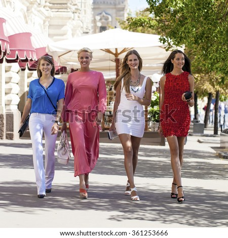 Portrait of a beautiful young four fashion women walk on summer city