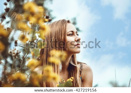 Portrait of a beautiful young girl contemplating among yellow flowers and clouds.