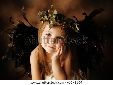 Portrait of a beautiful young girl dressed up as an angel with brown wings and a gold dress, wearing an ivy crown - stock photo