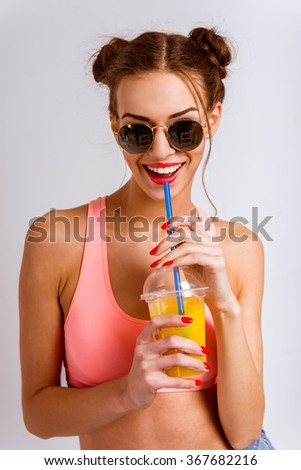 Portrait of a beautiful young girl drinking juice, isolated on gray background - stock photo