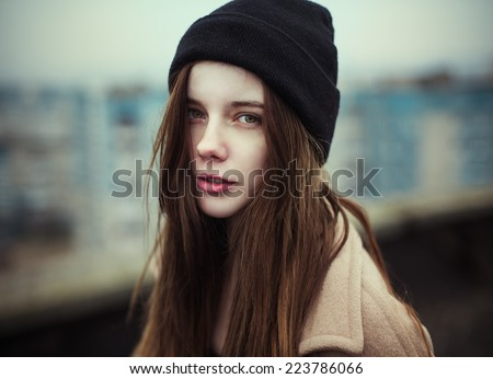portrait of a beautiful young girl in a hat hipster autumn on the roof in the city - stock photo