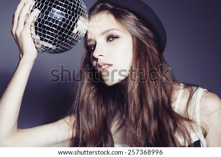 Portrait of a beautiful young girl in a hat with disco ball - stock photo