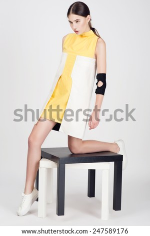 Portrait of a beautiful young girl in stylish dress in the studio on a white background - stock photo
