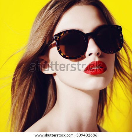 Portrait of a beautiful young girl in sunglasses in the studio on a yellow background - stock photo