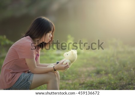 Portrait of a beautiful young girl is playing with teddy bear outdoor during sunset - stock photo