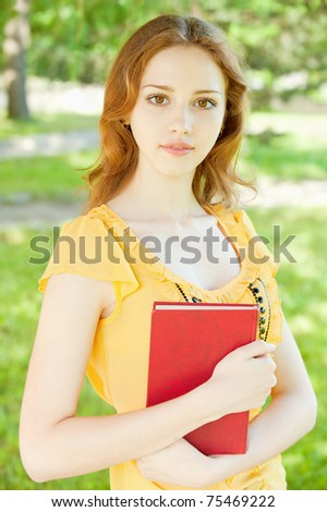 Portrait of a beautiful young girl-student with a book on the background of green nature