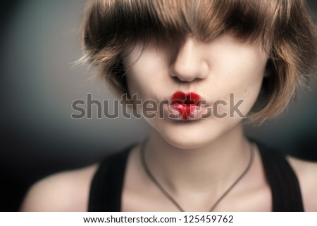 Portrait of a beautiful young girl with a heart on her lips
