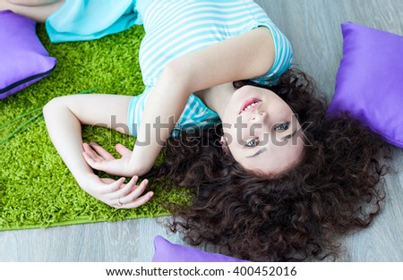 Portrait of a beautiful young girl with brown curly hair. Girl lying on the floor on a mat for meditation and looking at camera. Big green eyes. Pillows purple. Drink your morning coffee.  - stock photo