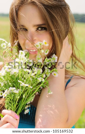 Portrait of a beautiful young girl with chamomile - stock photo