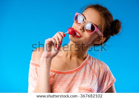 Portrait of a beautiful young girl with long curly hair with lollipops, isolated on blue background