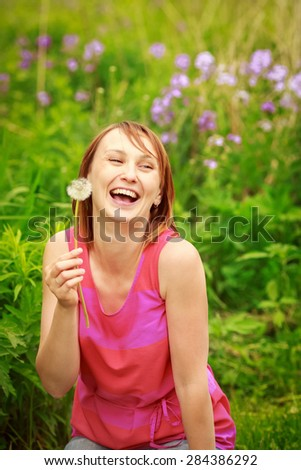 Portrait of a beautiful young girl woman sitting in the forest field meadow with dandelion flowers in her hands and laughing on a bright summer day, funny romantic card with copy space for text - stock photo