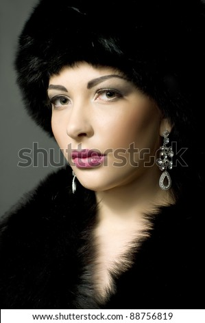 Portrait of a beautiful young lady in black fur - stock photo